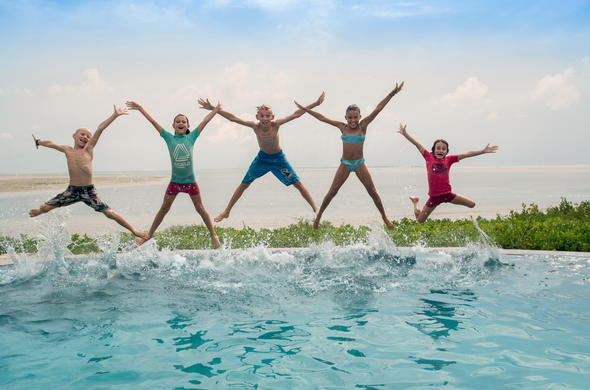 Kids having fun jumping in the pool during their Mozambique Family Holiday.
