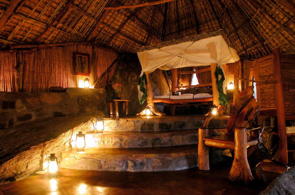 Spacious thatched bedroom with stone and bamboo accents.